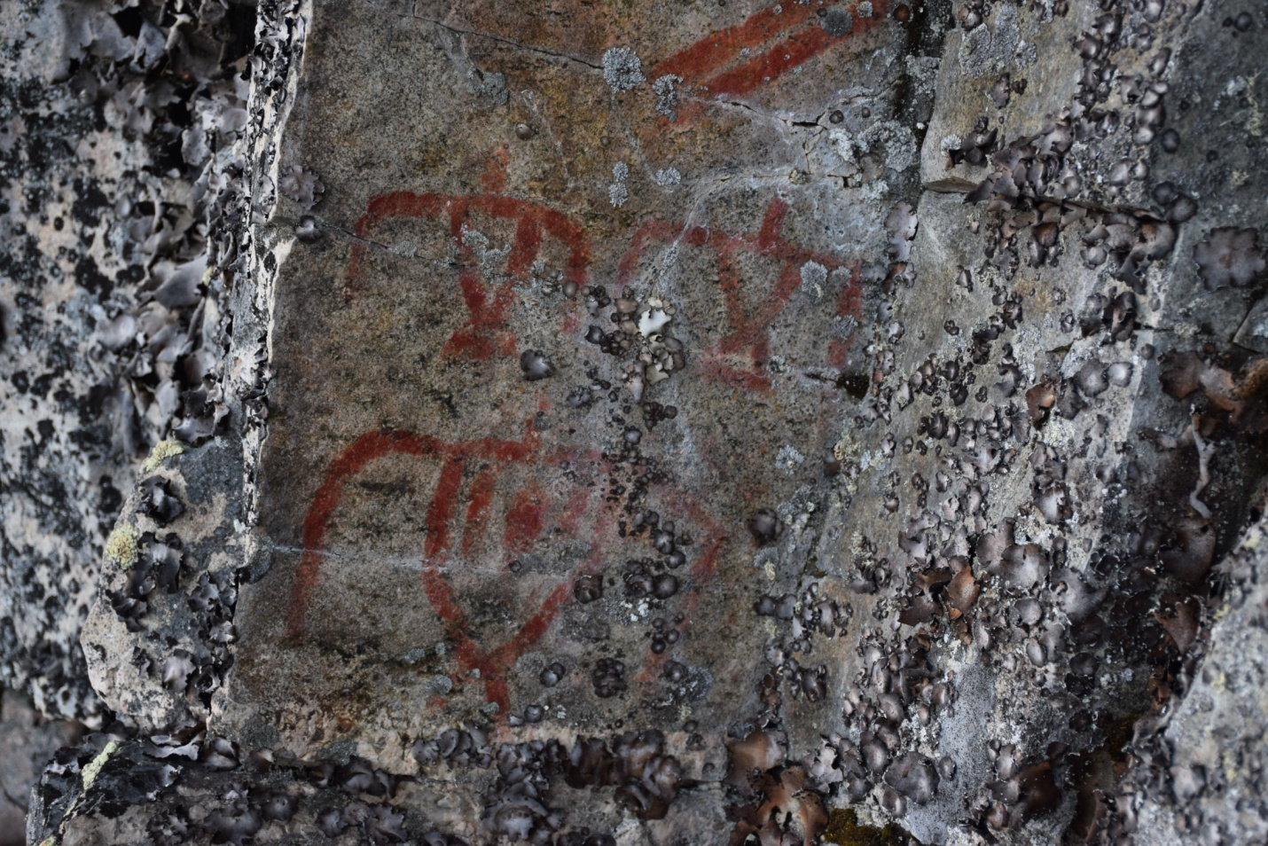 Picture of red ochre rock paintings representing three Thunderbirds at the Wizard Lake site, in Ontario, Canada